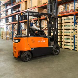 a lady in a warehouse loading pallets with doosan forklift