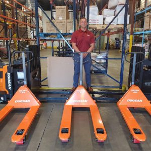 a man standing by pallet jacks by doosan