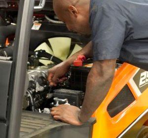 a service technician working on a doosan forklift